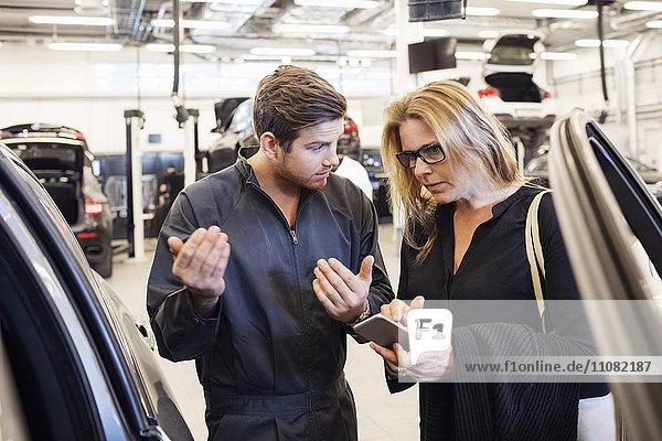 Mechaniker unterstützt den Kunden bei der Nutzung der mobilen App in der Kfz-Werkstatt