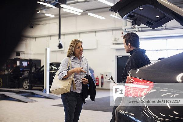 Kundengespräch mit Automechaniker in der Werkstatt