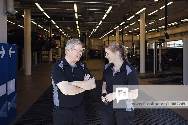 Zufriedene Experten diskutieren im Stehen in der Werkstatt