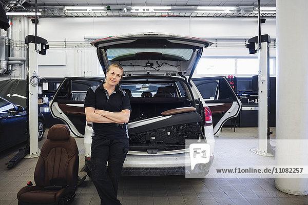 Porträt einer selbstbewussten Mechanikerin beim Anlehnen an ein Auto in der Werkstatt
