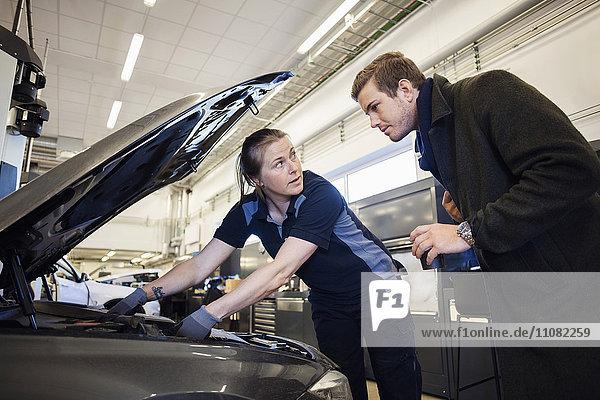 Mechanikerinnen reparieren Auto  während sie den Kunden in der Autowerkstatt anschauen.