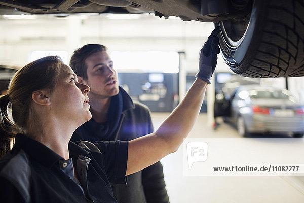 Nahaufnahme des Mechanikers  der das Rad dem Kunden in der Werkstatt zeigt.