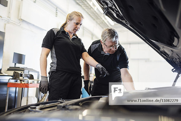Mechanikerin  die dem älteren Mann im Geschäft den Motor zeigt.