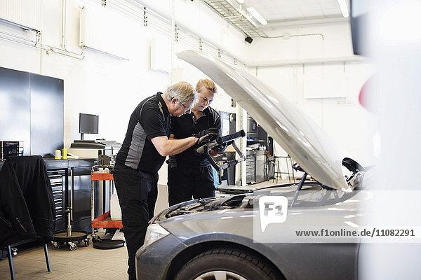 Fachmänner und -frauen  die bei der Untersuchung des Autos im Geschäft Technik einsetzen