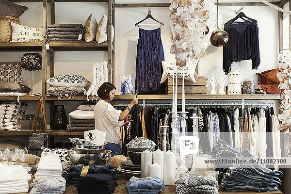 Die Besitzerin steht am Kleiderständer im Laden.