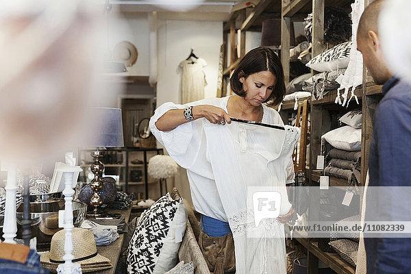 Abgeschnittenes Bild des Besitzers  der die Kundin beim Überprüfen des Kleides im Geschäft ansieht