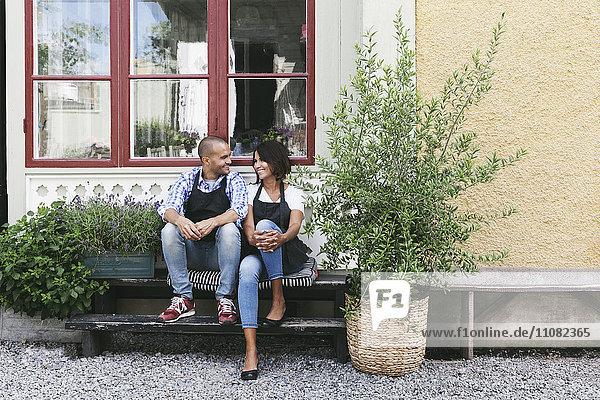 Lächelnde Besitzer sitzen auf einer Bank am Fenster vor dem Café