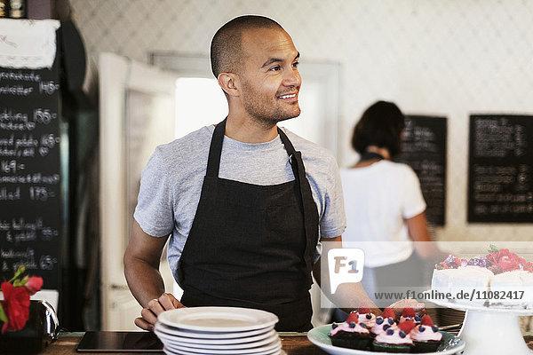 Lächelnder Bäcker am Cafe Tresen mit Mitarbeitern im Hintergrund