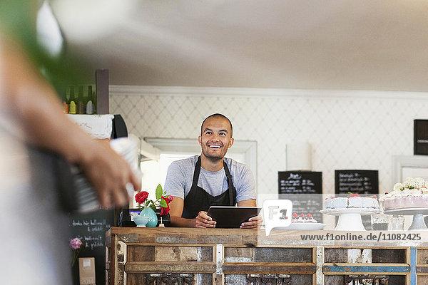 Lächelnder Bäcker mit digitalem Tablett beim Anblick einer Kollegin im Café