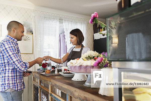 Kunde gibt Kreditkarte an Besitzerin am Cafe-Schalter ab