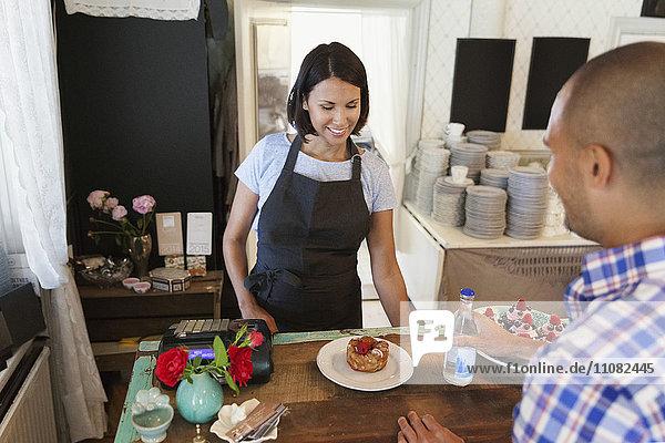 Lächelnde Frau schaut in die Wüste  während der Mann am Tresen im Café steht.