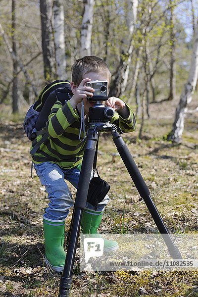 Boy taking photo in forest