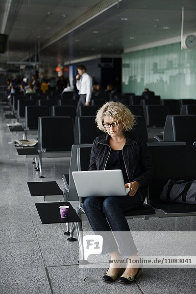 Mature woman with laptop at airport  Frankfurt  Germany