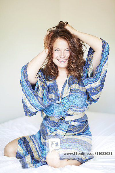 Smiling young woman on bed wearing bathrobe