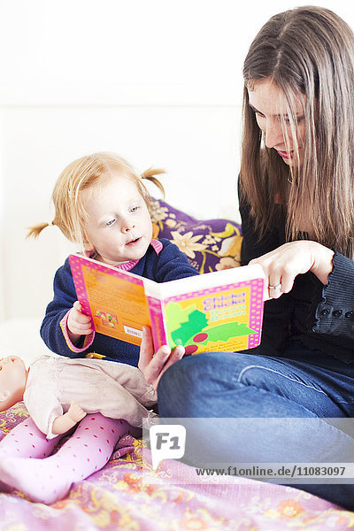 Mother and daughter reading book together