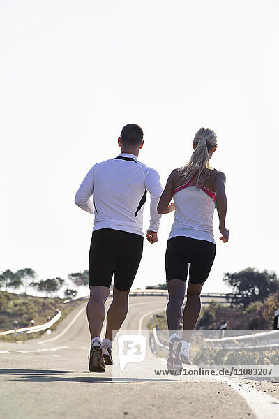 Couple running on road  rear view