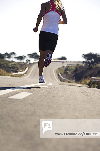Young woman running on road