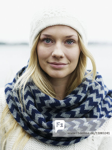 Portrait of young woman wearing muffler and knit hat