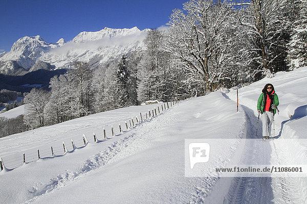 Frau geht auf schneebedecktem Feld gegen die Berge