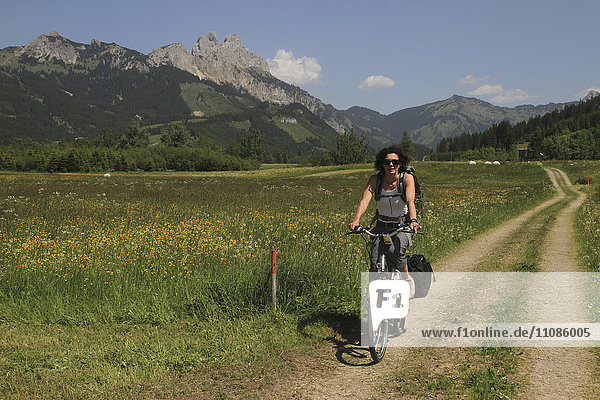 Frau fährt Fahrrad auf der Straße durch Grasfeld gegen Berge