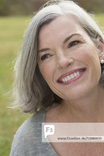 Close-up of thoughtful mature woman smiling outdoors