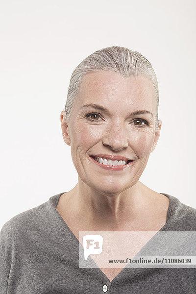 Porträt einer glücklichen reifen Frau vor weißem Hintergrund