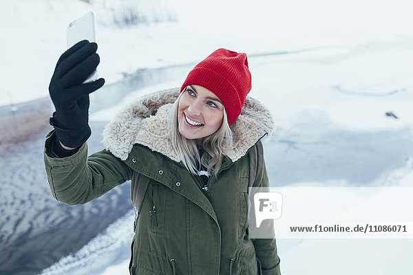 Happy young woman taking selfie on smart phone during winter