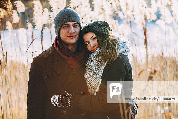 Junges Paar umarmt sich im Stehen auf dem Feld