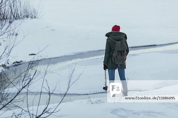 Frau mit Rucksack  die die Kamera hält  während sie im Winter auf dem Feld steht.