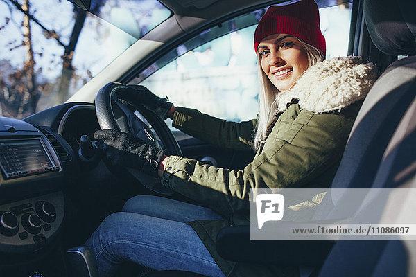 Porträt einer glücklichen jungen Frau in warmer Kleidung beim Autofahren