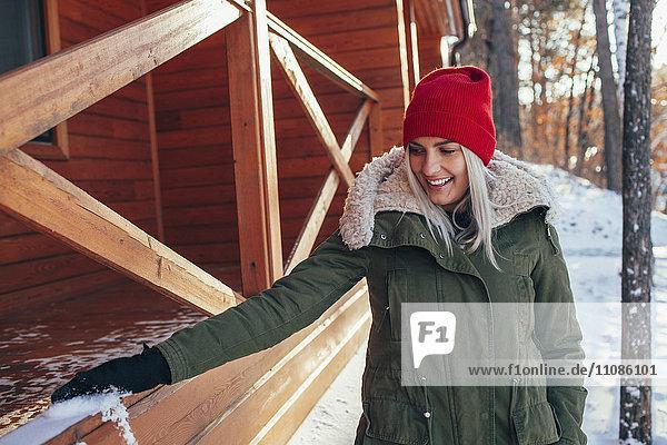 Schöne junge Frau entfernt Schnee vom Geländer