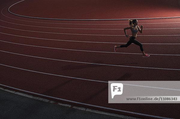 Hochwinkelansicht einer jungen Athletin auf der Rennstrecke Hochwinkelansicht einer jungen Athletin auf der Rennstrecke
