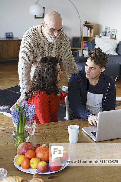 Teenager talking to parents while using laptop at home