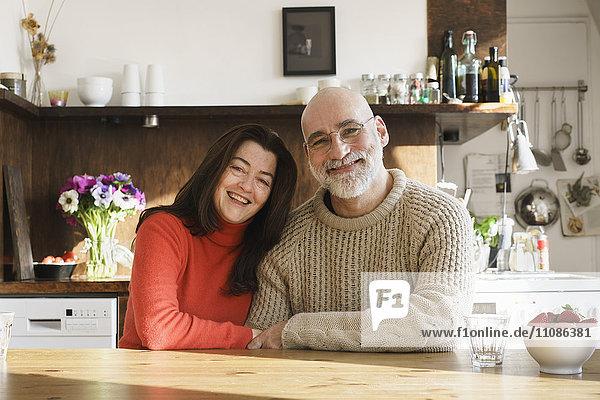 Porträt eines reifen Paares  das zu Hause am Tisch sitzt