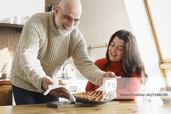 Der reife Mann serviert der Frau zu Hause Kuchen auf dem Tisch.