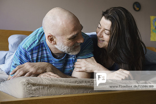 Nahaufnahme eines reifen Paares  das zu Hause auf dem Bett liegt.