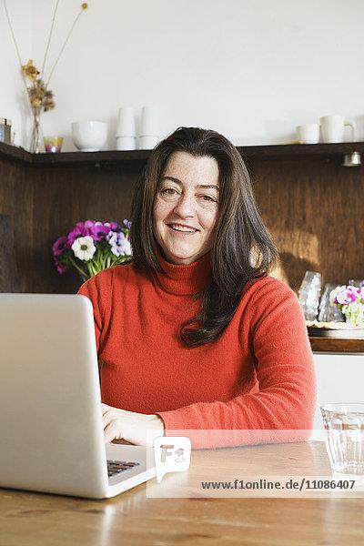 Porträt der lächelnden reifen Frau mit dem Laptop zu Hause