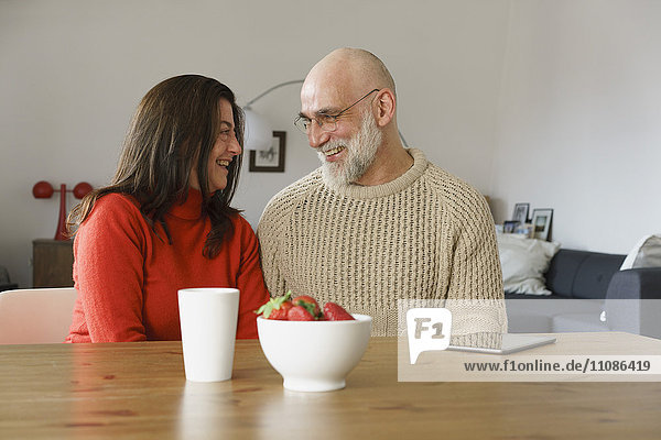 Smiling mature couple looking face to face while sitting at home