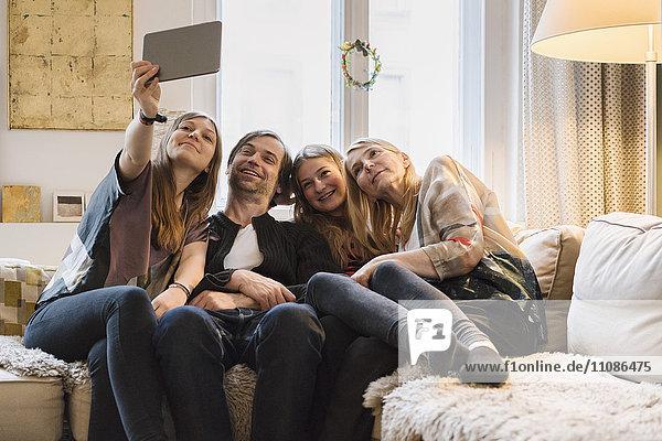 Glückliche vierköpfige Familie  die Selfie zu Hause durch ein digitales Tablett nimmt.