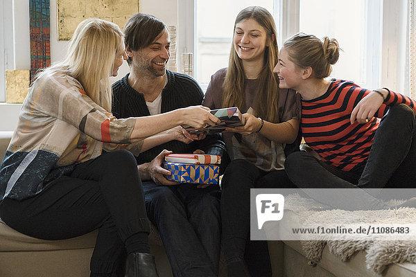 Glückliche Familie schenkt Tochter im Wohnzimmer