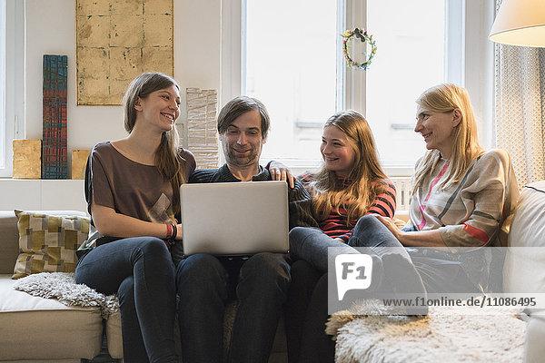 Glückliche Familie mit Vater mit Laptop im Wohnzimmer