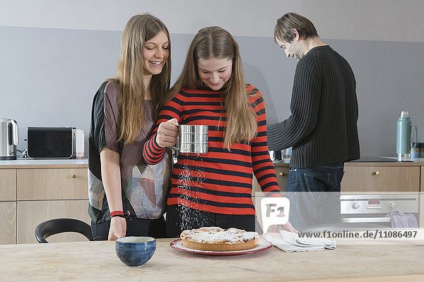 Young woman watching sister sprinkling tart with icing sugar in kitchen