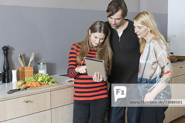 Eltern mit Tochter beim Kochen mit dem digitalen Tablett in der Küche