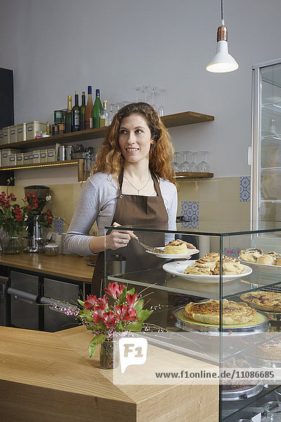 Young woman serving cinnamon rolls while standing at cafe