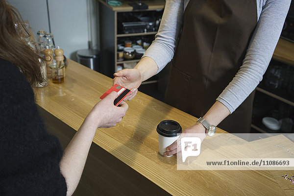 Woman paying owner with credit card at cafe