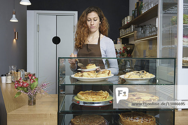 Front view of woman serving cinnamon rolls while standing at cafe