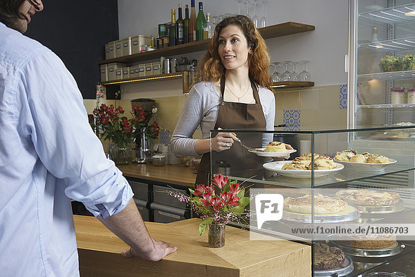 Woman looking at man while serving cinnamon rolls at cafe