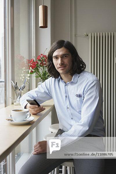Porträt eines Mannes mit Smartphone beim Kaffeetrinken im Cafe