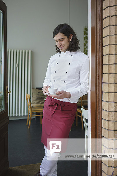 Smiling chef holding coffee cup while standing at doorway