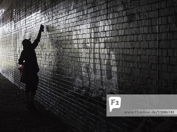 Seitenansicht der Person Spritzlackierung an der Wand